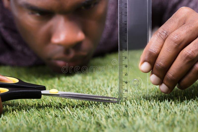 O homem que corta a grama medida com Scissor fotos de stock