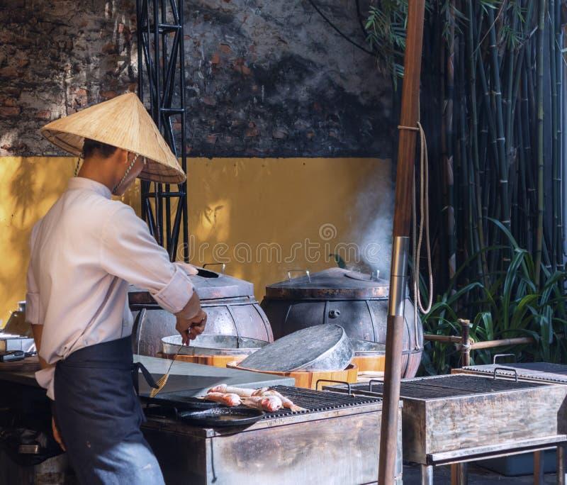 O homem que cozinha uma grade fritou peixes no restaurante local em um mercado de rua fotos de stock royalty free