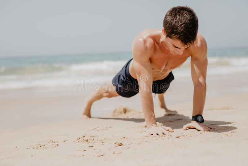 O homem que da aptidão exercitar empurra levanta o sorriso feliz Cruz-treinamento masculino do modelo da aptidão na praia foto de stock