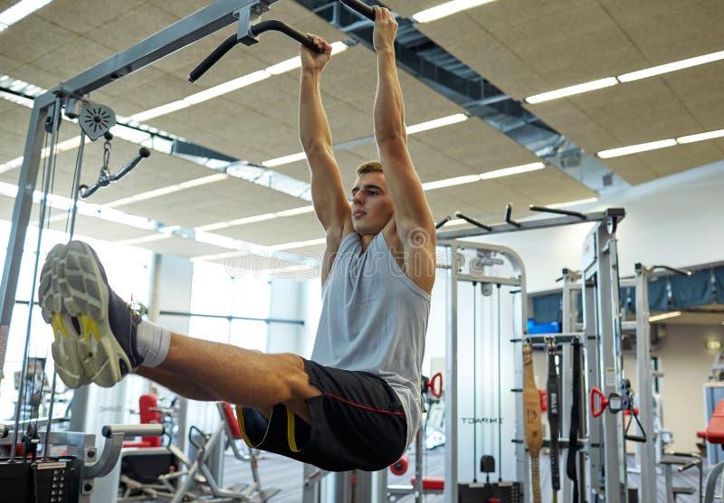 O homem que dobra os músculos abdominais levanta sobre a barra fotos de stock