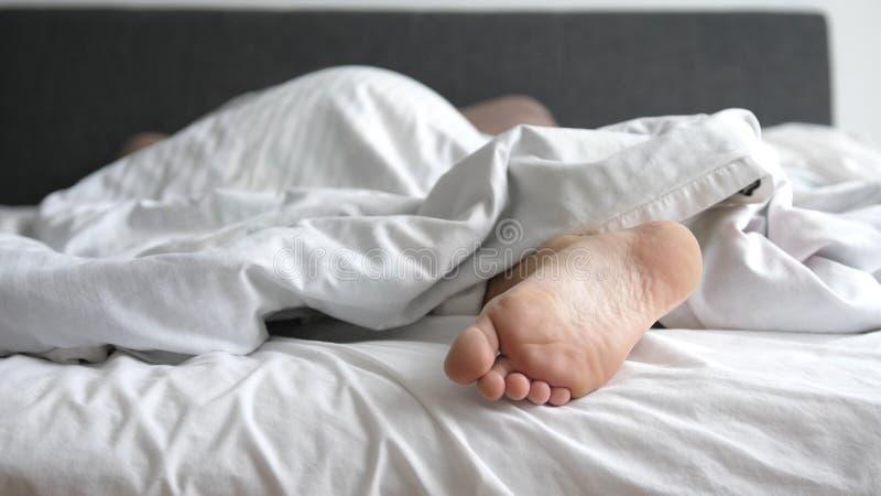 O homem que dorme nos pés da cama relaxa em feriados Feche acima de seu pé fotografia de stock royalty free