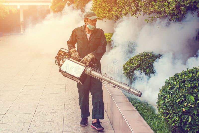 O homem que enevoa-se para eliminar o mosquito para impede a febre de dengue da propagação fotos de stock