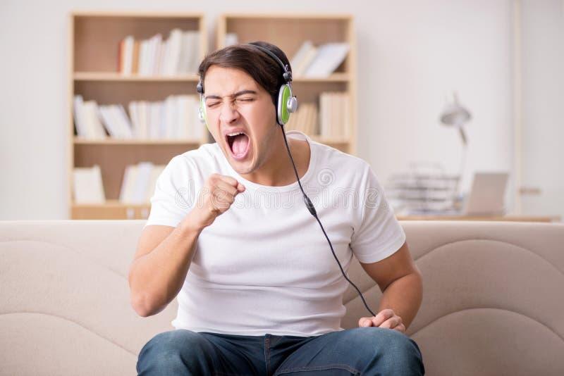 O homem que escuta a música em casa imagens de stock