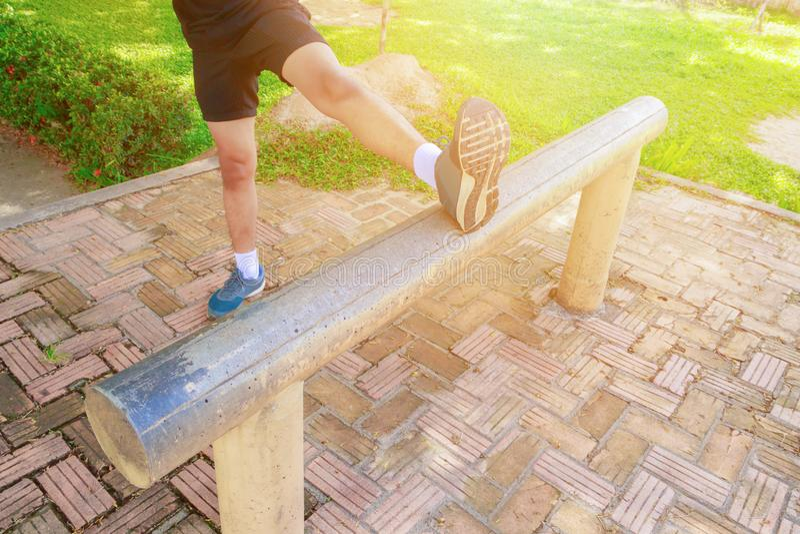 O homem que estica os pés muscles antes de correr movimentando em público o parque fotografia de stock royalty free