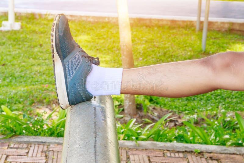 O homem que estica os pés muscles antes de correr movimentando em público o parque fotos de stock