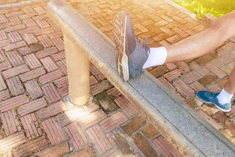 O homem que estica os pés muscles antes de correr movimentando em público o parque imagens de stock