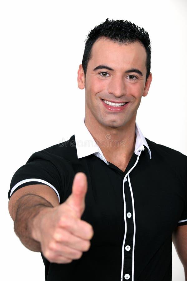O homem que faz os polegares levanta o sinal imagem de stock