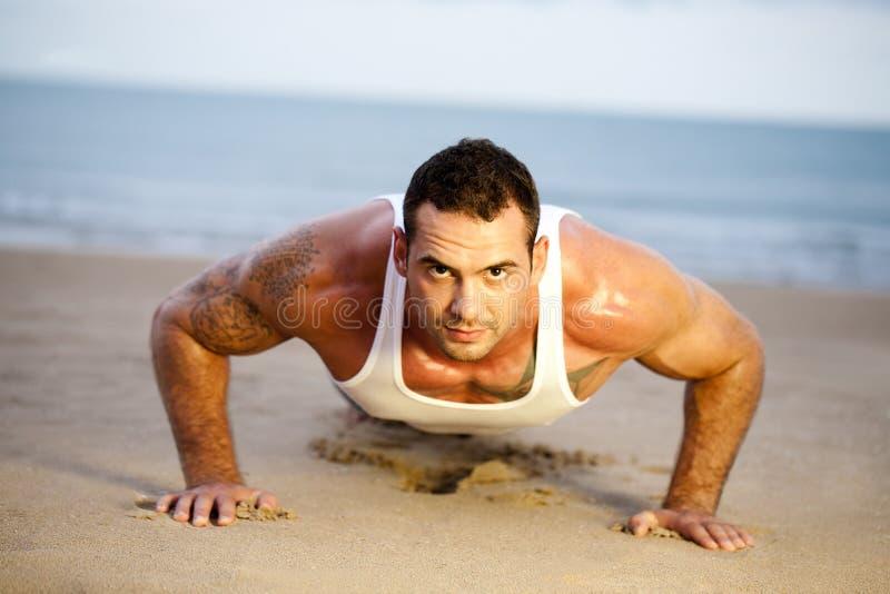 O homem que fazer empurra levanta em uma praia imagens de stock