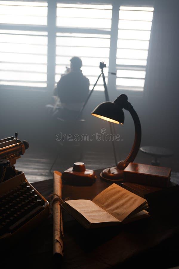 O homem que o fotógrafo examina o filme no fotógrafo do lightman examina o filme na luz imagem de stock
