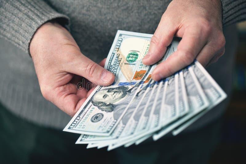 O homem que guarda cédulas dos dólares do dinheiro foto de stock