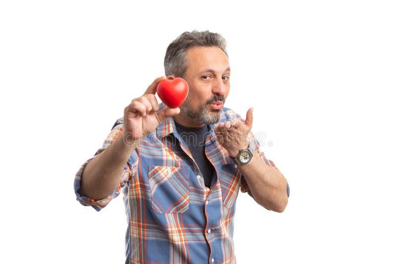 O homem que guarda o coração e que faz envia o gesto dos beijos fotos de stock