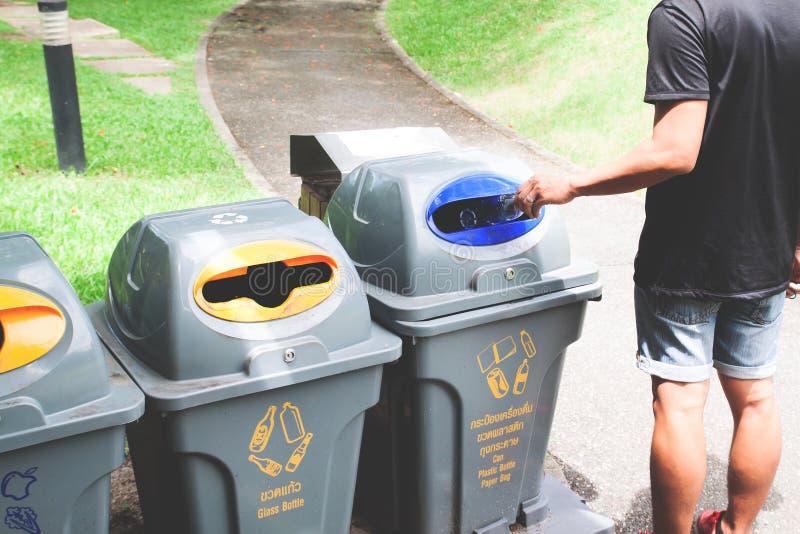 O homem que joga a garrafa plástica recicla dentro o balde do lixo imagem de stock