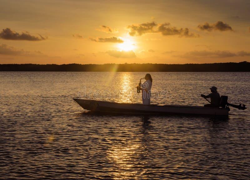 O homem que joga o saxofone em uma navigação do barco nas águas do Praia faz a praia de Jacaré fotos de stock royalty free