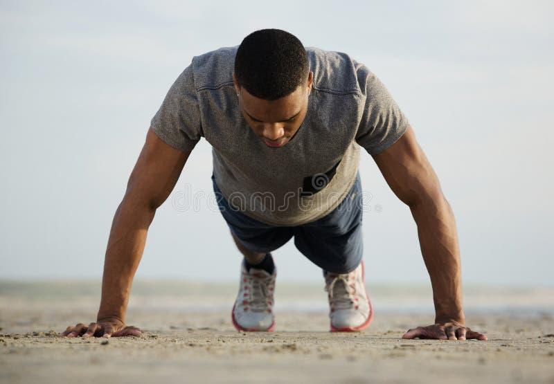 O homem que novo apto fazer empurra levanta na praia fotos de stock
