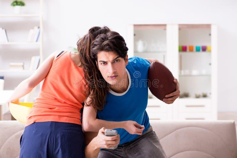 O homem que olha o futebol americal com sua esposa imagens de stock royalty free