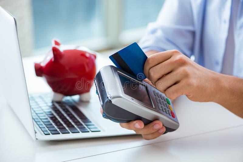 O homem que processa a transação do cartão de crédito com terminal da posição fotos de stock royalty free