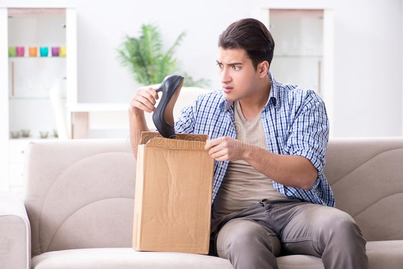 O homem que recebe o pacote errado com as sapatas fêmeas da mulher fotos de stock