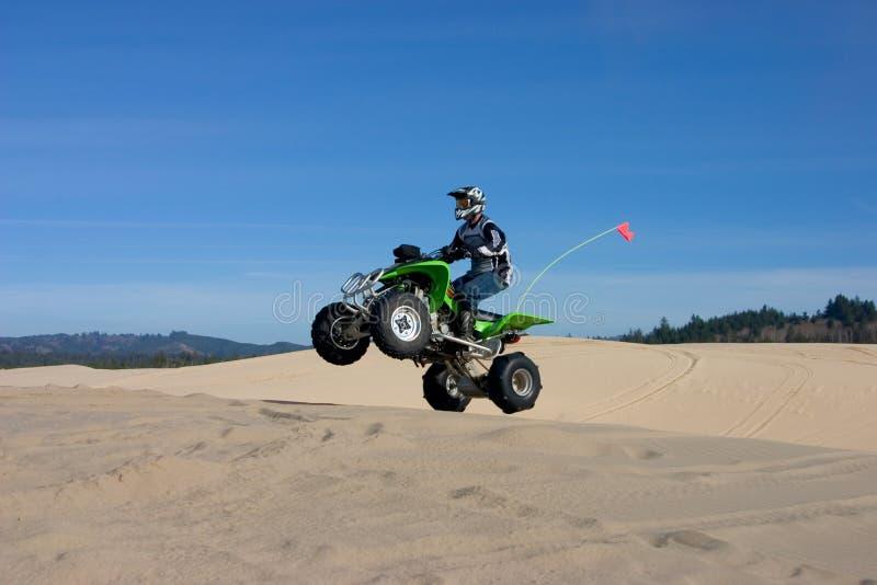 O homem que salta ATV em dunas de areia foto de stock royalty free