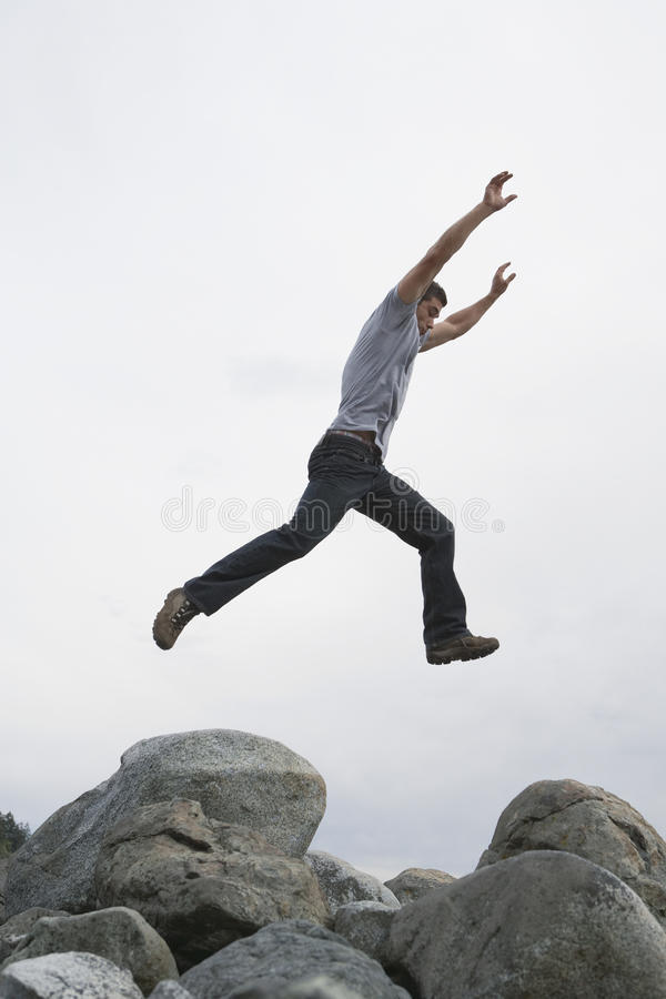 O homem que salta com os braços aumentados sobre a rocha foto de stock royalty free