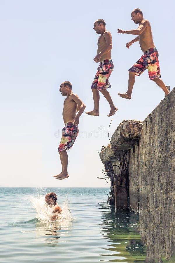 O homem que salta do cais fotos de stock
