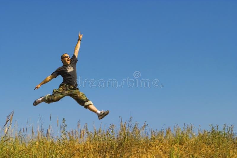 O homem que salta em um prado fotos de stock royalty free