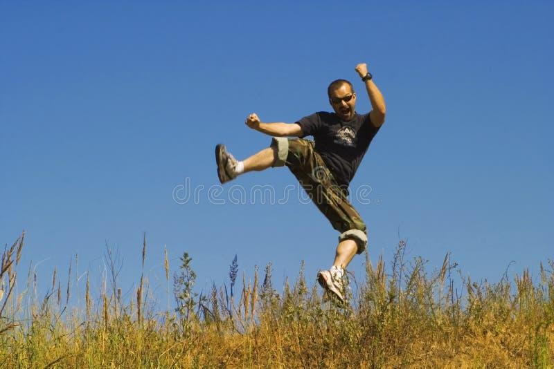 O homem que salta em um prado foto de stock royalty free