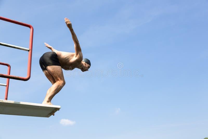 O homem que salta fora da placa de mergulho na piscina fotos de stock