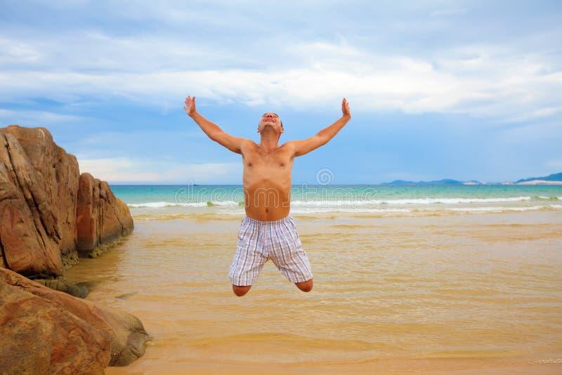 O homem que salta na praia imagem de stock royalty free