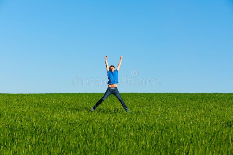 O homem que salta no campo verde imagem de stock royalty free