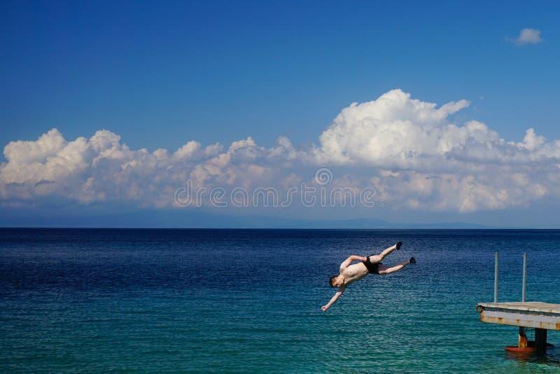 O homem que salta no mar do cais imagens de stock