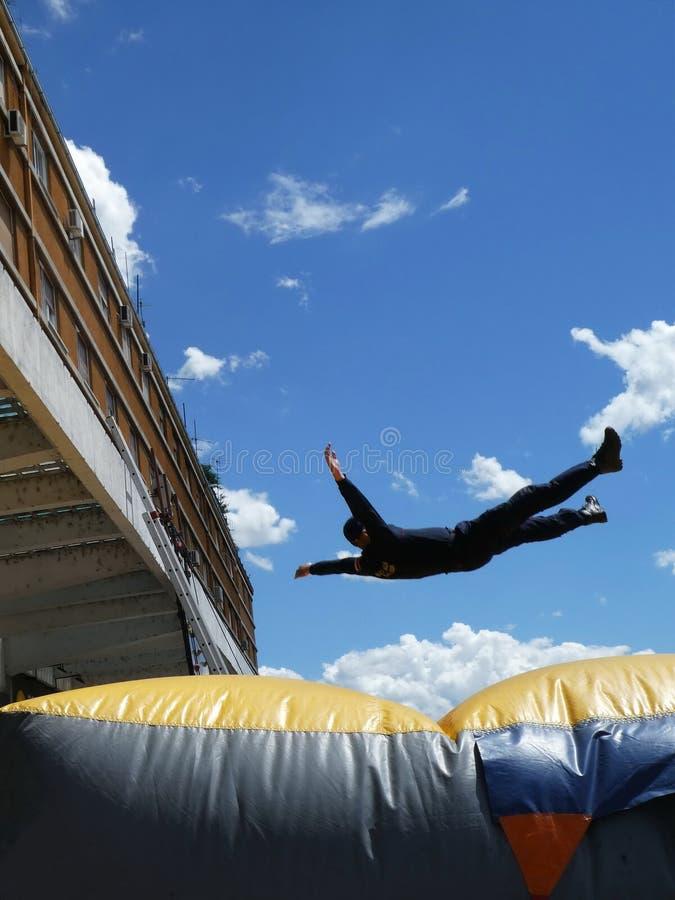 O homem que salta para baixo ao coxim infl?vel do salvamento igualmente conhecido como um coxim do salto - pessoa de salvamento fotografia de stock