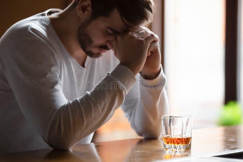 O homem que senta-se no contador da barra sente bebida bebendo deprimida do álcool fotos de stock royalty free