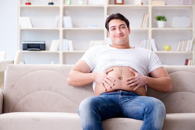 O homem que sofre do peso extra no conceito da dieta fotografia de stock royalty free