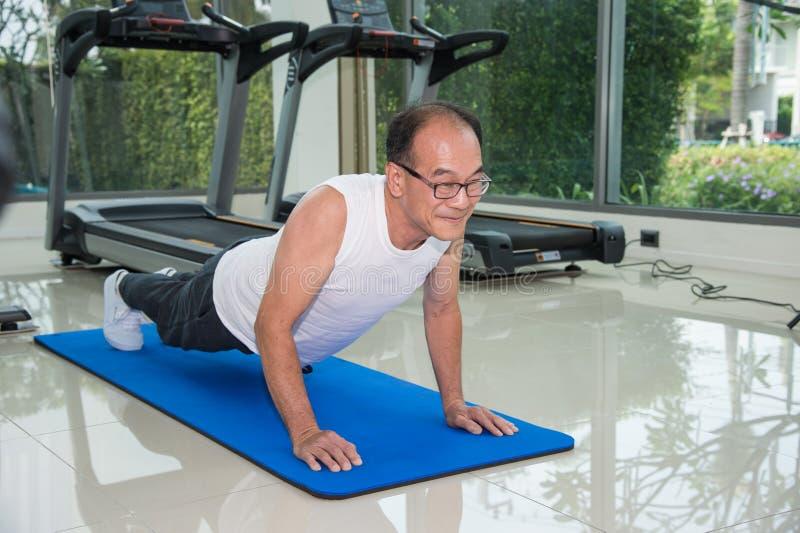 O homem que superior a aptidão que exercita fazendo empurra levanta no fitness center imagem de stock