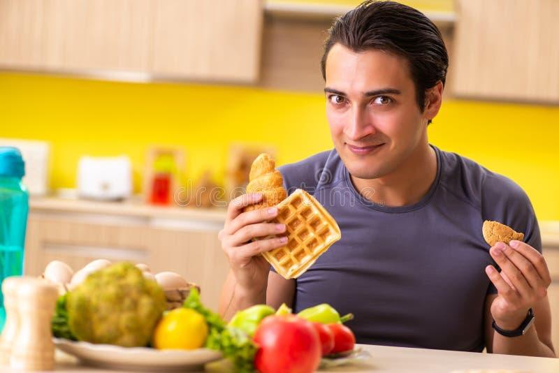 O homem que tem a escolha dura entre o alimento saudável e insalubre imagem de stock