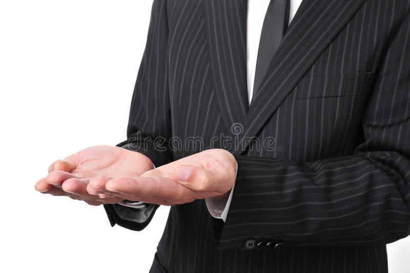 O homem que veste um terno com suas mãos abre como mostrando ou guardando o som imagens de stock royalty free