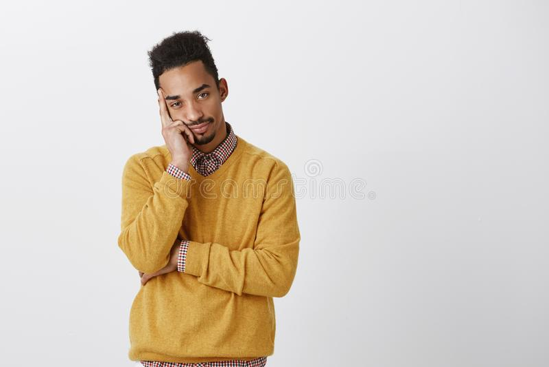 O homem quer ser em outro lugar Homem novo atrativo incomodado com cabeça de inclinação do penteado afro na palma, sentindo furad fotos de stock