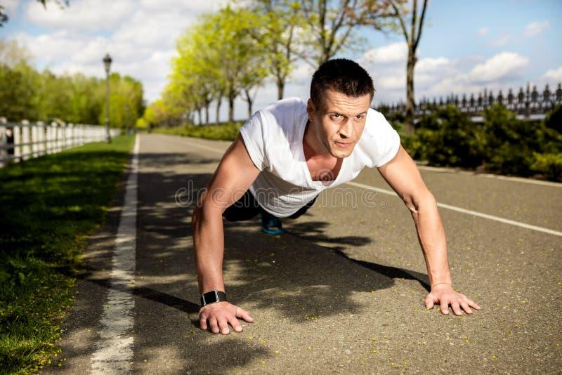 O homem rasgado está exercitando em pectorals na natureza foto de stock