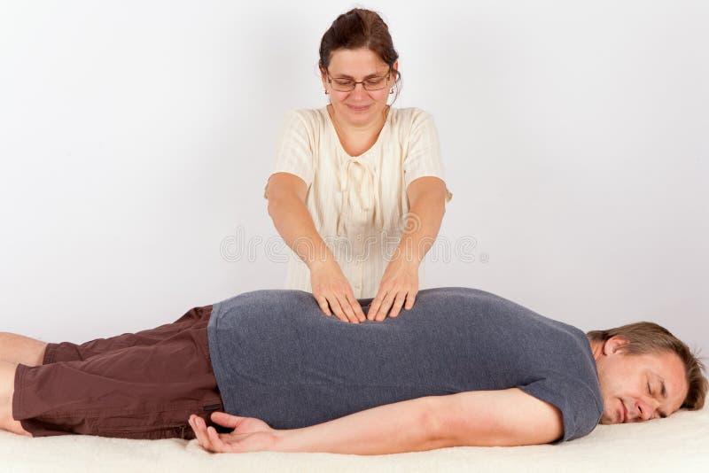 O homem recebe a terapia de Bowen similar à massagem traseira imagens de stock