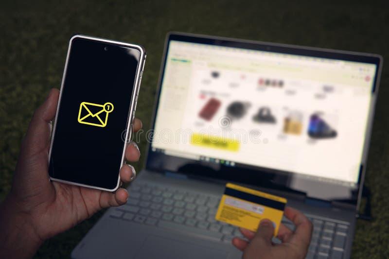 O homem recebeu uma mensagem curto no smartphone que é em linha no Web site shooping através do portátil e que guarda o cartão de fotografia de stock royalty free