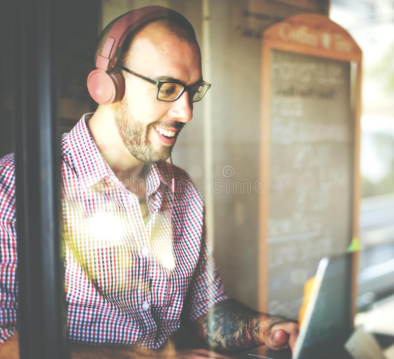 O homem relaxa a apreciação que escuta usando o conceito do portátil foto de stock
