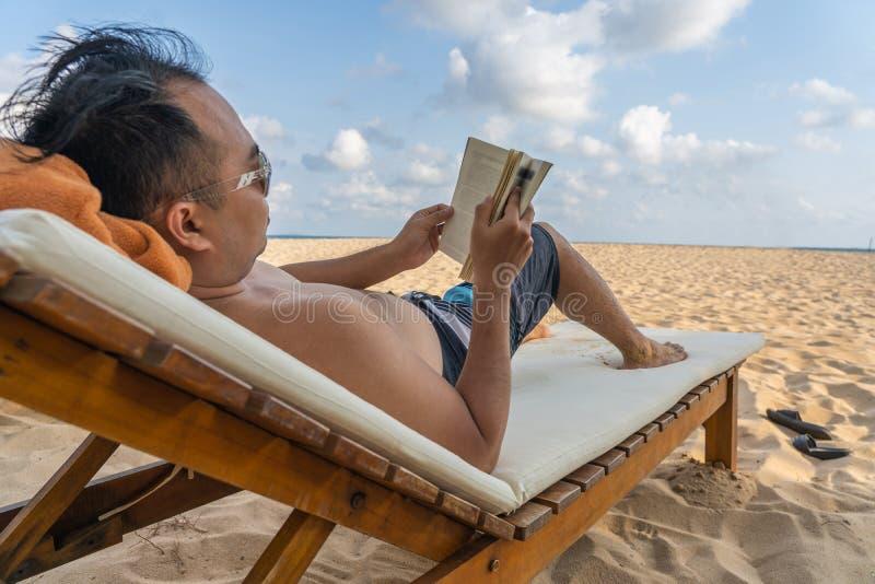 O homem relaxa na praia e lê um livro fotos de stock royalty free