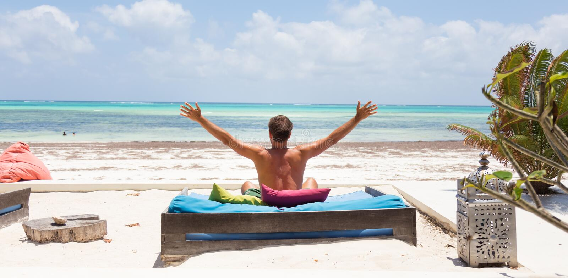 O homem relaxado no vadio luxuoso, braços rised, apreciando férias de verão na praia bonita fotografia de stock