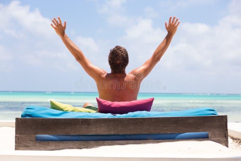 O homem relaxado no vadio luxuoso, braços rised, apreciando férias de verão na praia bonita imagem de stock