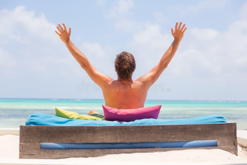 O homem relaxado no vadio luxuoso, braços rised, apreciando férias de verão na praia bonita imagens de stock