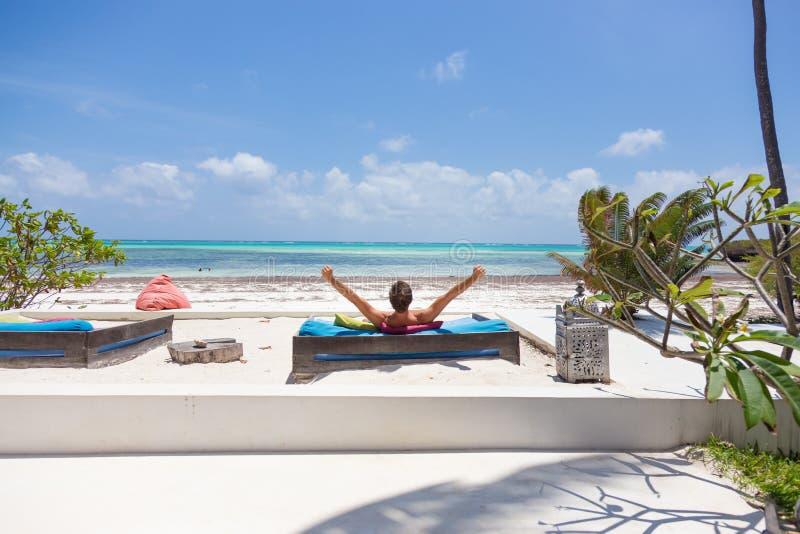 O homem relaxado no vadio luxuoso, braços rised, apreciando férias de verão na praia bonita imagem de stock royalty free