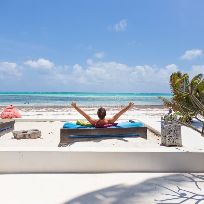 O homem relaxado no vadio luxuoso, bra?os rised, apreciando f?rias de ver?o na praia bonita imagens de stock