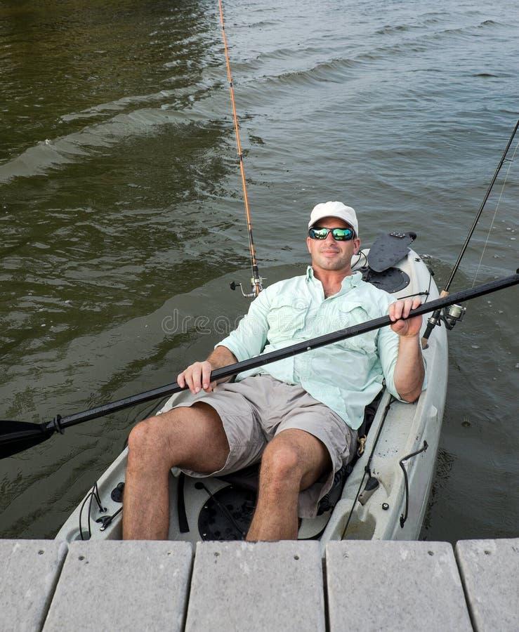 O homem relaxado retrocede para trás no caiaque da pesca imagem de stock royalty free