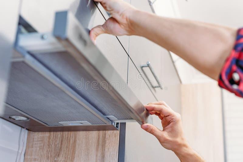 O homem repara a capa na cozinha Filtro da substituição na capa de fogão fotos de stock