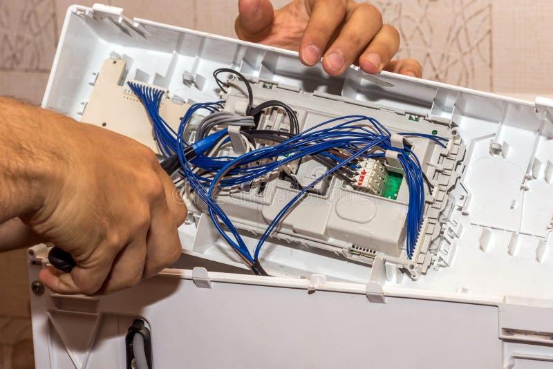 O homem repara a eletrônica da máquina de lavar foto de stock royalty free